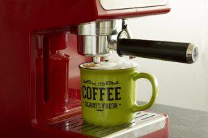 Buitinės technikos remontas, kavos aparatas purškia į puodelį kavą su pieno puta