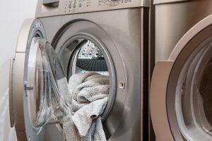 Buitinės technikos remontas, pilkas frotinis rankšluostis kyšo pro praviras skalbimo mašinos dureles